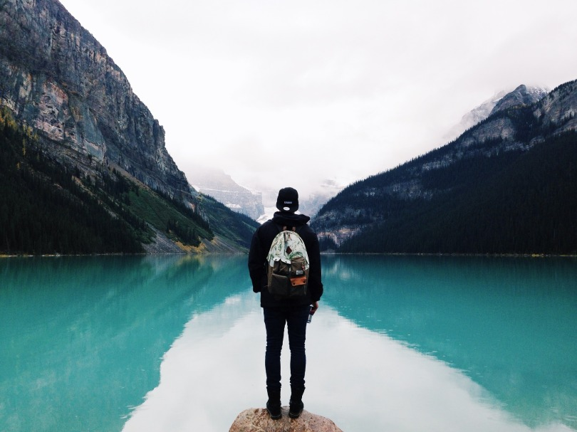 A lone wanderer, staring out onto a lake - with a valley ahead of them.